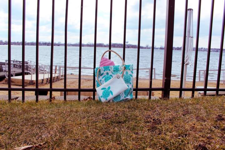 Sea Bag Sea Turtle bag next to balck fence by a lake