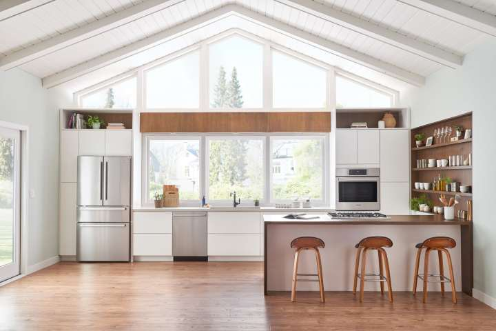 Large white and wood kitchen that is well lit.