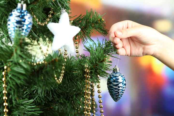 Decorating Christmas tree on bright background - avoid holiday stress