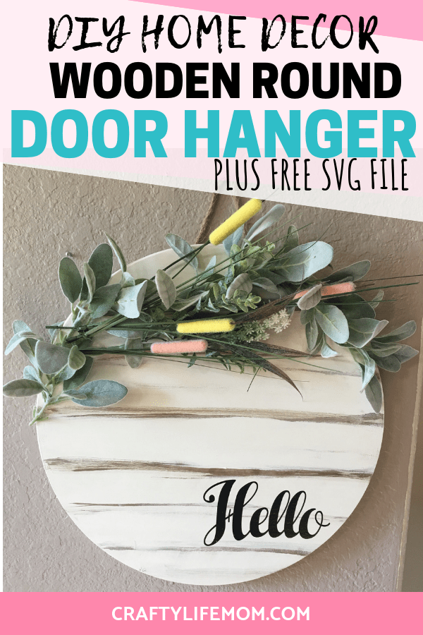 Create this DIY wooden round door hanger using items form your local hardware store and florals form the dollar tree. With just a little bit of paint and this FREE SVG cut file you can create this Spring look for your home foyer or front door. #rounddoorhanger #homedecor