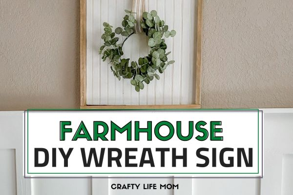 Learn how to recreate this beautiful farmhouse wreath sign using scrapbook wood and easy to nail trim and a wreath. This tutorial explains hows to use a scrap piece of wood for you to create this look in your home.  #farmhousewreathsign #farmhousedecor #diyfarmhouse
