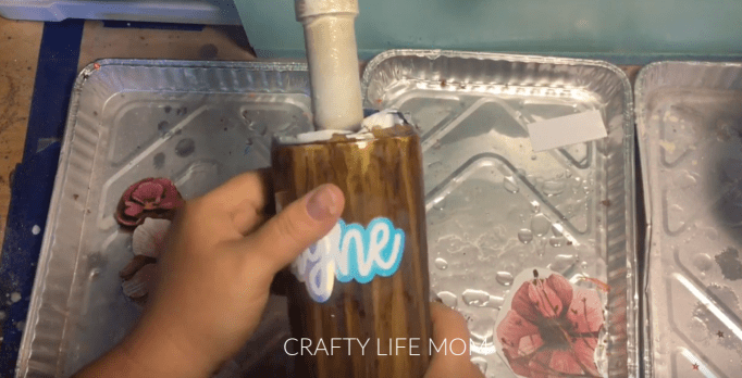 Learn how to create a wood grain epoxy tumbler using this method. She teaches you how step by step.