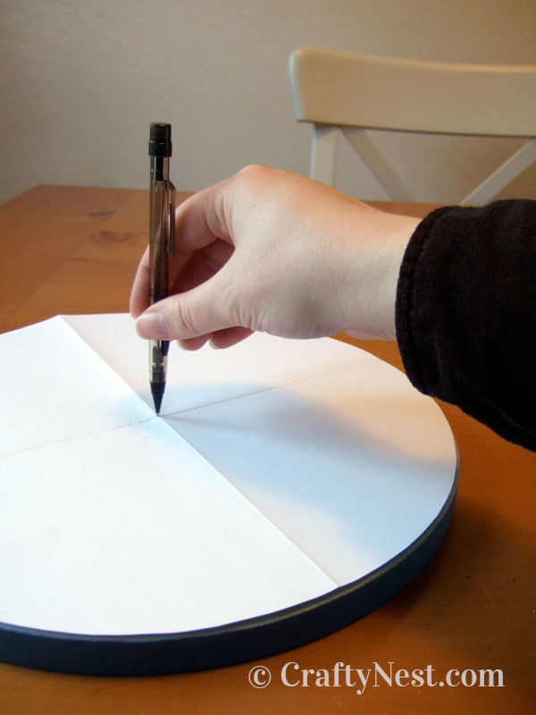 Finding the center of the clock face with a folded piece of paper, photo