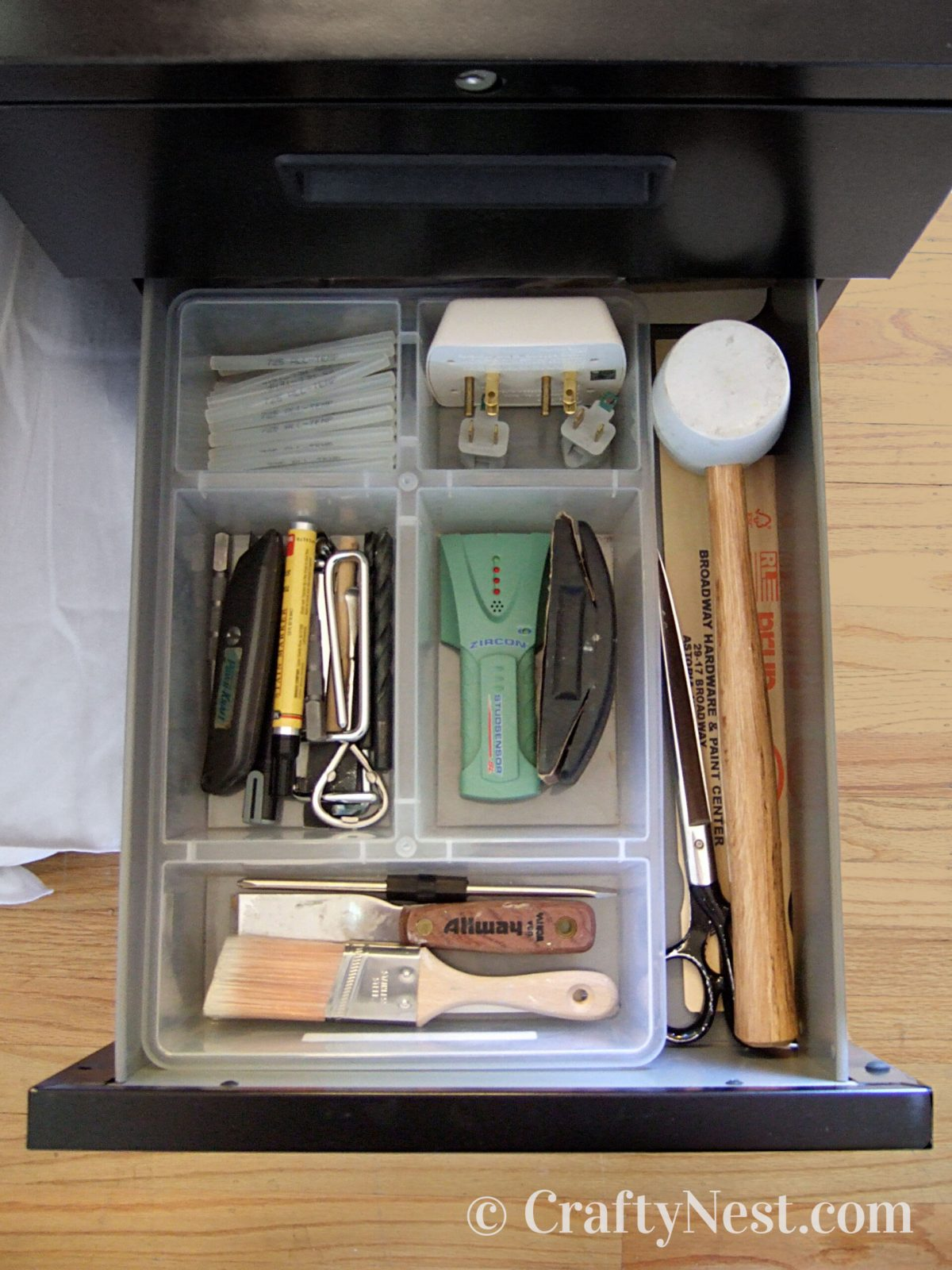 Open file cabinet drawer with tools organized inside, photo