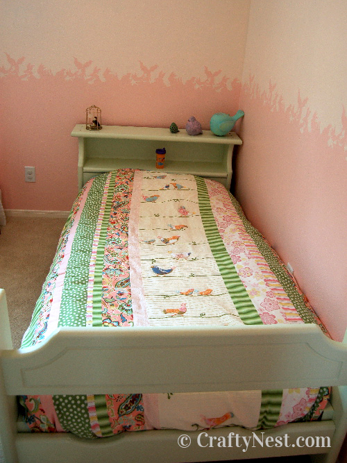 Green and pink bed with pink stenciled wall, photo