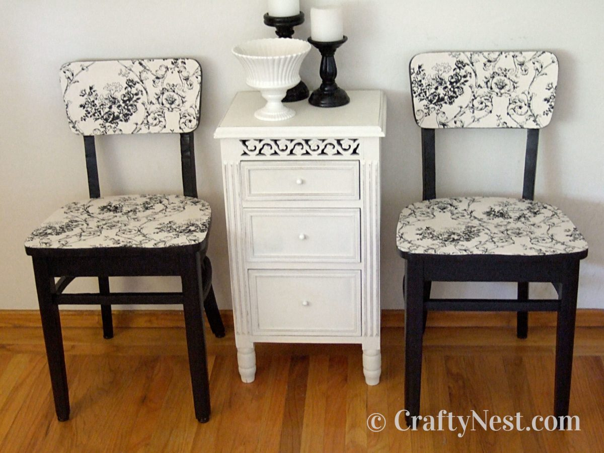 Two black and white dining chairs with end table, photo