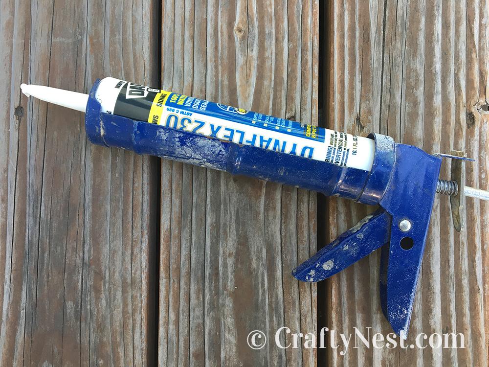 Dynoflex 230 white caulk in a caulking gun, photo