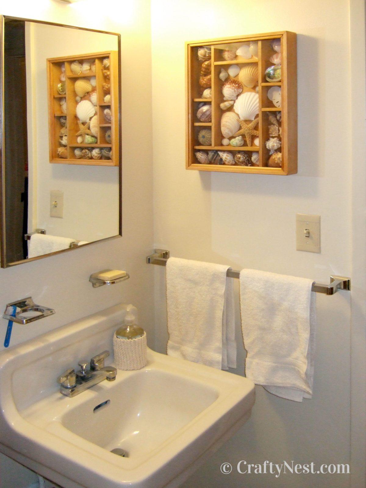 Shadow box with seashells on the bathroom wall, photo