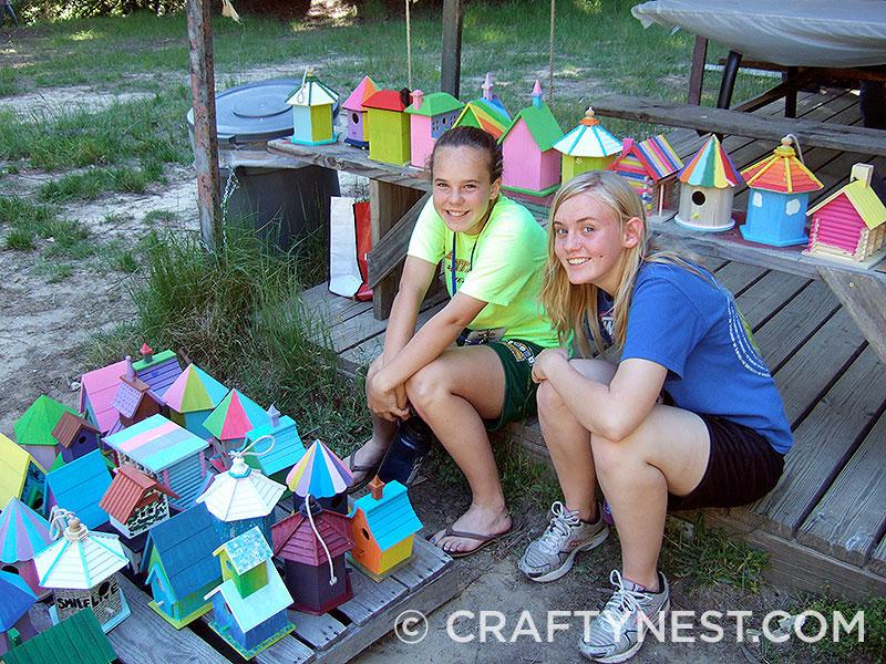 Two girls sit among dozens of birdhouses.
