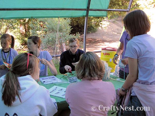 Girls making paracord bracelets at camp, photo