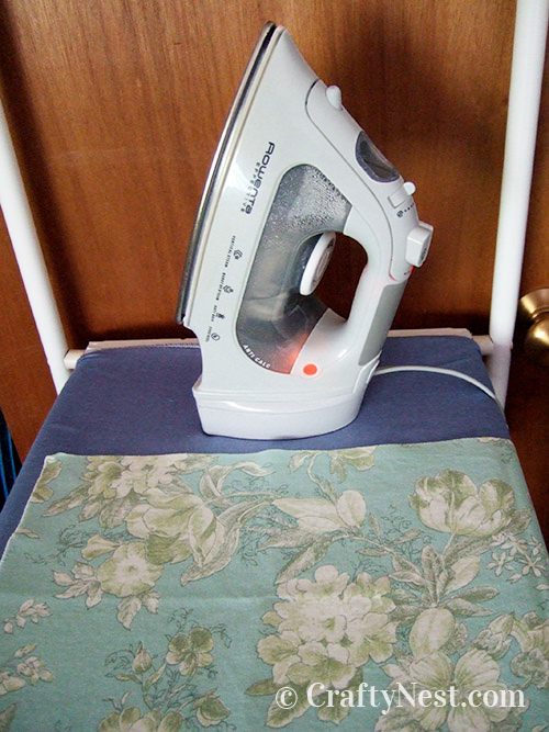 Fabrci on an ironing board with iron, photo