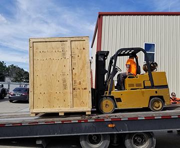 forklift loading crate on flatbed