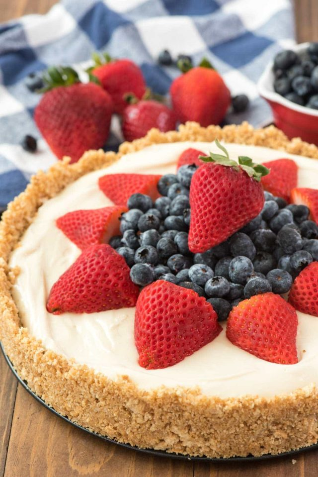 Best No Bake Cheesecake Recipe Ever Topped With Blueberries And Strawberries On A Wooden Board