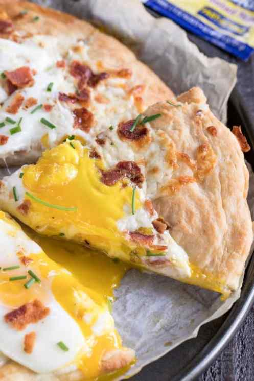 slice of homemade breakfast pizza with egg and bacon
