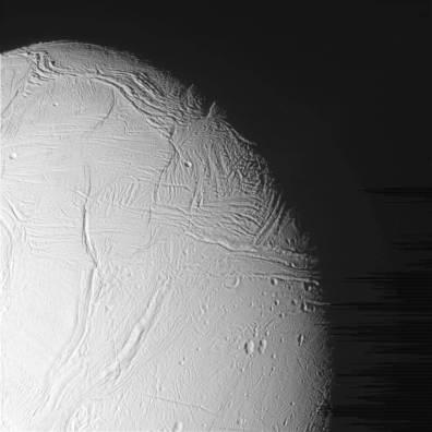 Lodowa powierzchnia Enceladusa sfotografowana przez sondę Cassini. Na nieobrobionym zdjęciu po prawej widoczne są artefakty w postaci ciemniejszych linii. Fot. NASA/JPL-Caltech/Space Science Institute