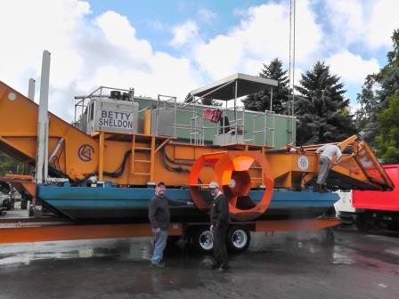 Paul Swanson, Chautauqua Lake Association general manager, and Randy Sweeney, Chautauqua Region Community Foundation executive director, pose in front of a harvester as it is removed from Chautauqua Lake at the conclusion of the CLA's season. The CLA removed over 2,000 tons of vegetation and debris from Chautauqua Lake this summer.