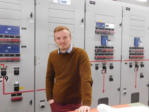 Jarrett Devereaux standing in front of circuit breakers in a switch gear line-up at the Board of Public Utilities' Chadakoin substation. Image courtesy of the Jamestown Board of Public Utilities.