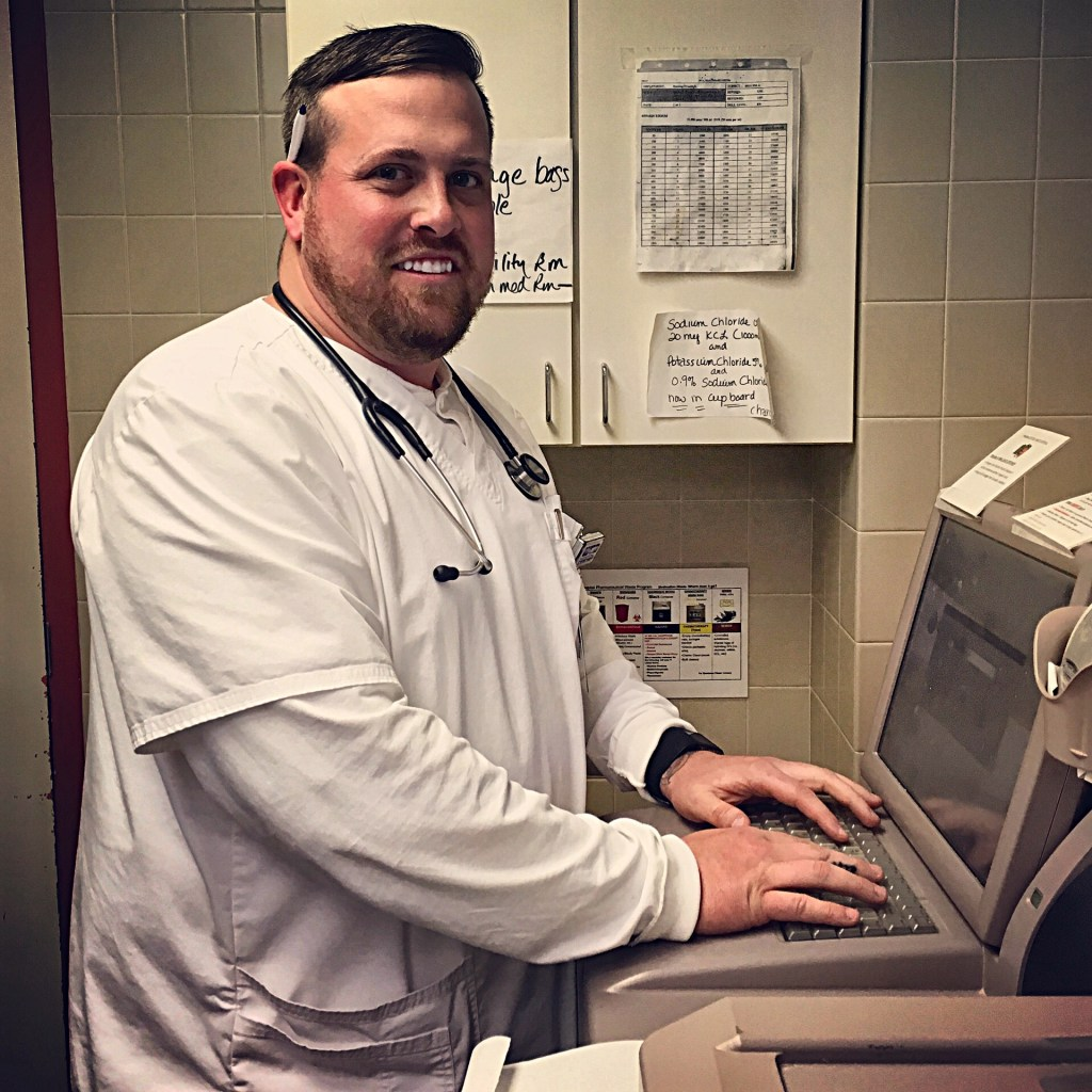 Trevor Mullard, RN, enters patient information into the Pyxis Medstation, a machine that communicates with the hospital's pharmacy to dispense medication.
