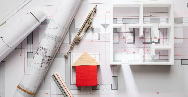 Construction concept. Residential building drawings and architectural model