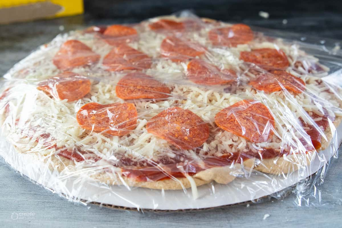 pepperoni pizza on cardboard round covered with plastic wrap