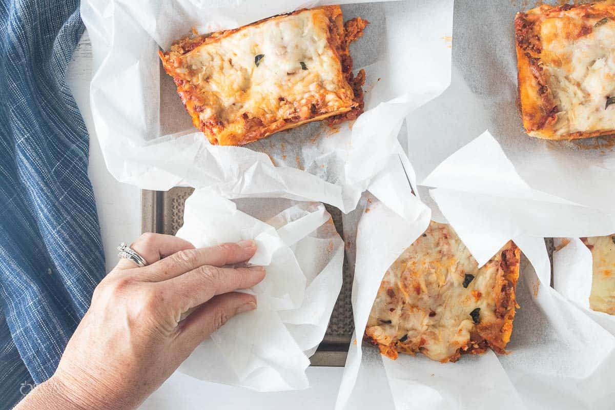 slices of lasagna wrapped in parchment paper