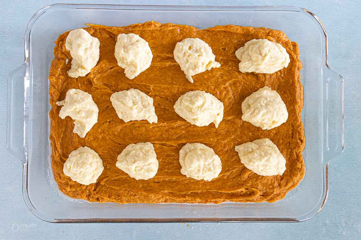 pumpkin spread on bottom of baking dish with drops of batter