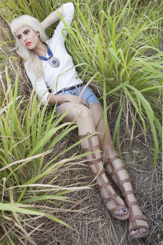 Blonde model reclining in tall grass in cut-off denim shorts and gladiator sandals.