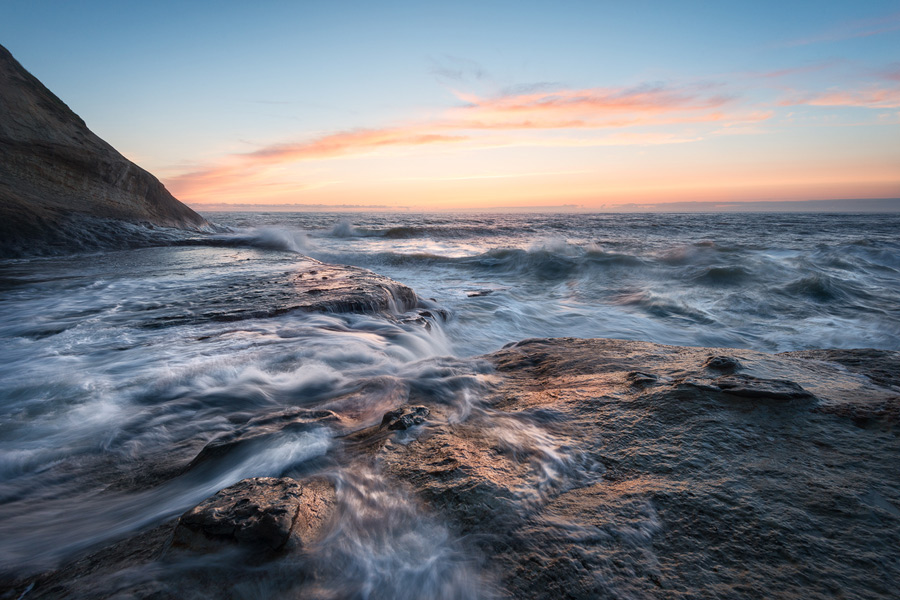 A long exposure photo of the sea at sunset