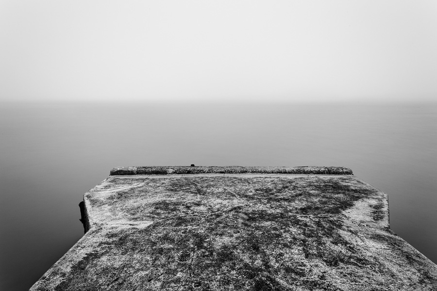 Black and white landscape photo of pier in the fog in Island Bay, Wellington