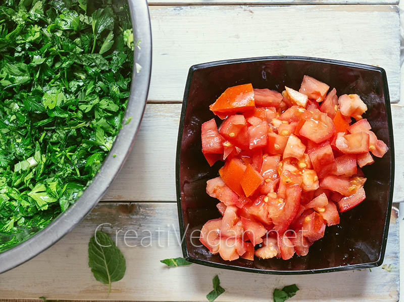 Ingredientes para hacer tabbouleh: tomates picados y perejil