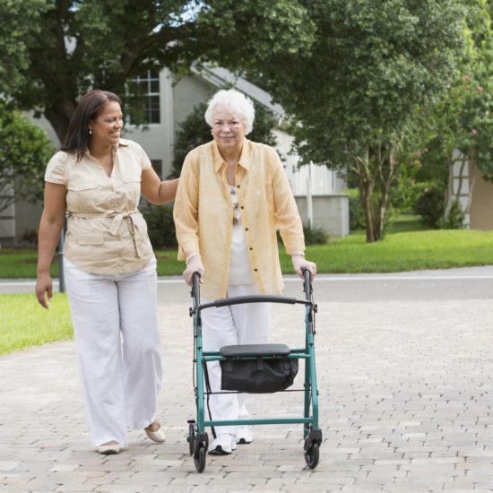 Senior Hispanic woman (70s) with caregiver (50s) in driveway of home.