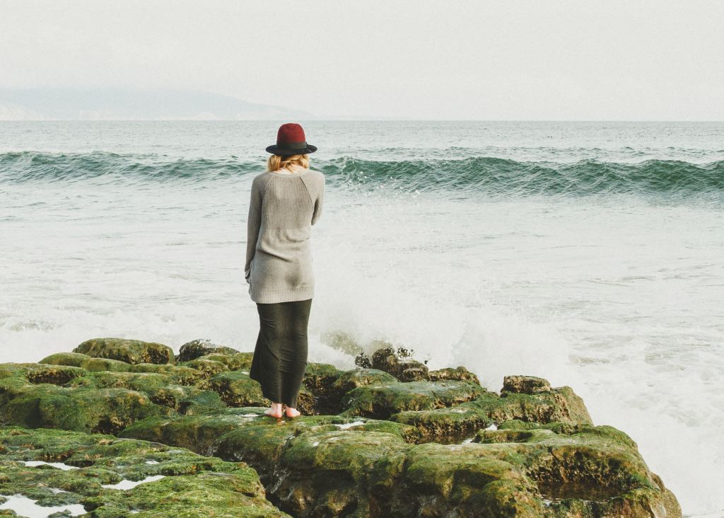 woman standing on an ocean shore with nowhere to go