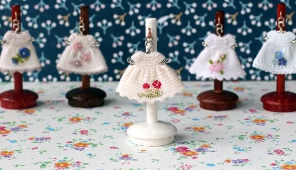 Miniature white dresses to dollhouse dolls