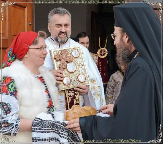 Bernadette Reut in rumänischer Landestracht begrüßte Weihbischof Dr. Sofian von Kronstadt traditionsgemäß mit Brot und Salz gemeinsam mit ihrem Mann Pfarrer Vasile Florin Reut, der das Evangeliar und das Kreuz reichte