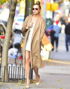 Pregnant Chrissy Teigen rocks A Beige Coat with Tight White Dress in sexy High Heels