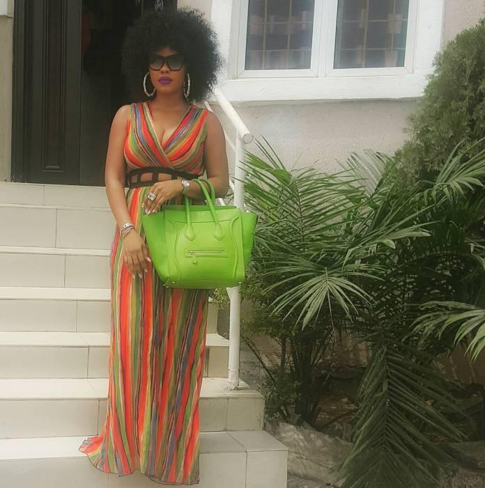 Daniella Okeke Rocks Afro Hair style with A slick Lemon Green Hand Bag
