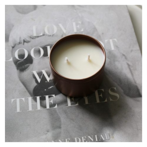 Doulble wick candle in a copper container on top of a book