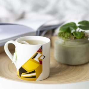 Fine bone china mug with a geometric Goldfinch Print. Mug is placed on a tray with tea bag label visible