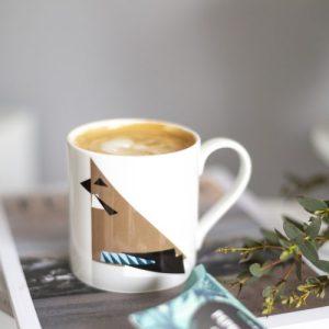 Fine bone china mug with a geometric Jay Print. Mug is placed on a magazine filled with coffee