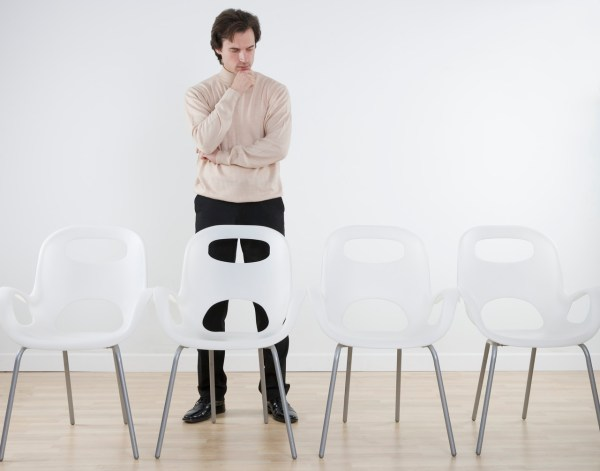 Thinking Businessman Staring at Empty Chairs
