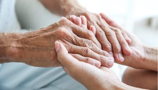 Young woman holding senior man hands, closeup