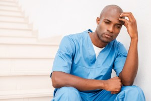 Feeling tired and depressed. Depressed young African doctor in blue uniform touching his head with hand and looking away while sitting at the staircase