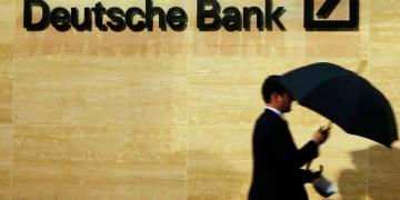 A man walks past Deutsche Bank offices in London December 5, 2013. REUTERS/Luke MacGregor (BRITAIN - Tags: BUSINESS)