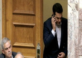 Greece's Prime Minister Alexis Tsipras speaks from his mobile phone during emergency Parliament session for the government's proposed referendum in Athens, Saturday, June 27, 2015. Greece's place in the euro currency bloc looked increasingly shaky on Saturday, when eurozone countries rejected a monthlong extension to its bailout program and the prime minister called for a risky popular vote on the country's financial future. (AP Photo/Petros Karadjias)
