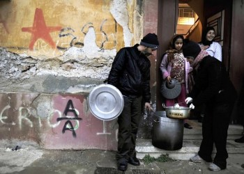 Activists of a  soup kitchen deliver food to an immigrant family in a poor neighborhood in Athens, on February 6, 2012. Greece today began constructing a fence on its border with Turkey to keep out thousands of undocumented migrants and refugees seeking to cross into Europe, the country's police minister said.  AFP PHOTO / LOUISA GOULIAMAKI