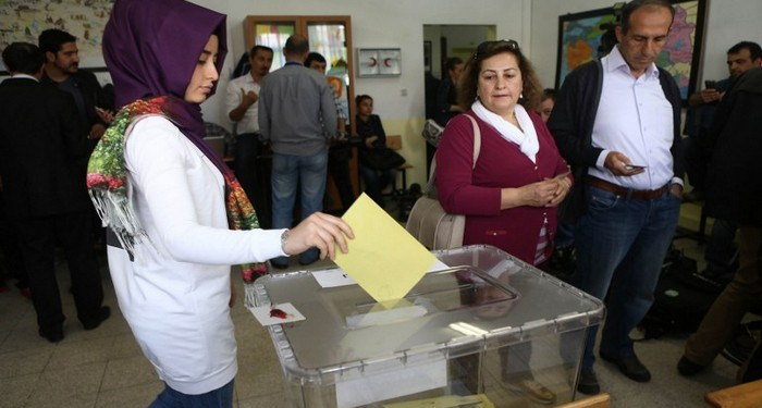 A Turkish woman casts her ballot as she votes in Turkey's general election at a polling station  in a primary school in Ankara on June 7, 2015. Turkey Turkish voters went to the polls on June 7 in a bitterly-contested election set to determine whether President Recep Tayyip Erdogan can tighten his increasingly controversial grip on the country. The legislative election is taking place under the shadow of violence after two people were killed and dozens more wounded in an attack on a rally of the pro-Kurdish People's Democratic Party (HDP) in the southeastern city of Diyarbakir two days prior. AFP PHOTO / ADEM ALTAN