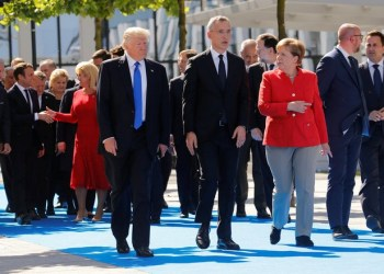 (L-R) U.S. President Donald Trump, NATO Secretary General Jens Stoltenberg and German Chancellor Angela Merkel gather with NATO member leaders to pose for a family picture before the start of their summit in Brussels, Belgium, May 25, 2017.REUTERS/Jonathan Ernst