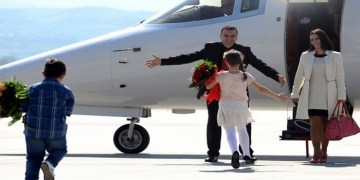 "Johan Tarculovski, center, accompanied by his wife Sonja Tarculovska, right, is welcomed by his children upon his arrival at ""Alexander the Great"" airport near Macedonia's capital Skopje, on Thursday, April 11, 2013. Couple of thousands of people have gathered at the airport on Tuesday to welcome the return of Johan Tarculovski, the only Macedonian convicted by The Hague tribunal for war crimes committed during 2001 ethnic conflict. (AP Photo/(Boris Grdanoski)"