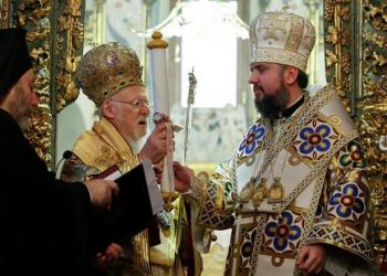 Ecumenical Patriarch Bartholomew I hands Tomos, a decree granting Ukraine church independence, to Metropolitan Epifaniy, head of the Orthodox Church of Ukraine, after the Epiphany mass at the Patriarchal Cathedral of St. George in Istanbul, Turkey January 6, 2019. REUTERS/Murad Sezer