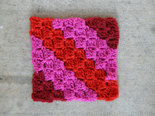 c2c crochet square in burgundy, pink, and red